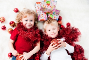 Cute siblings enjoying Christmas gifts